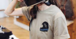 A tan t-shirt with a motorcycle helmet screen printed on the pocket.