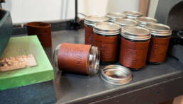 Mason jars wrapped in leather. Slow Down Coffee Co's logo is stamped in the leather.